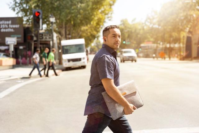 man walking across the street