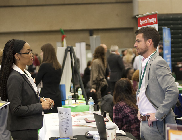 career fair with woman on left and man behind company table